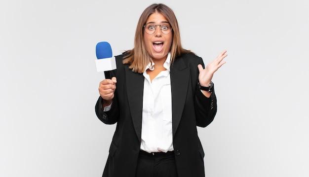 Jonge vrouwelijke verslaggever die zich blij, opgewonden, verrast of geschokt voelt, glimlacht en verbaasd is over iets ongelooflijks