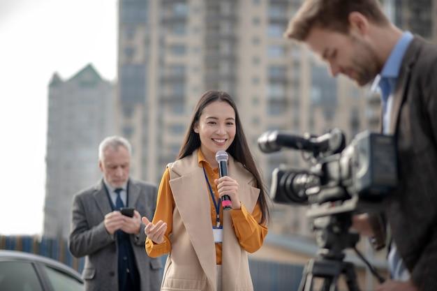 Jonge vrouwelijke verslaggever in een beige outfit praten met een camera