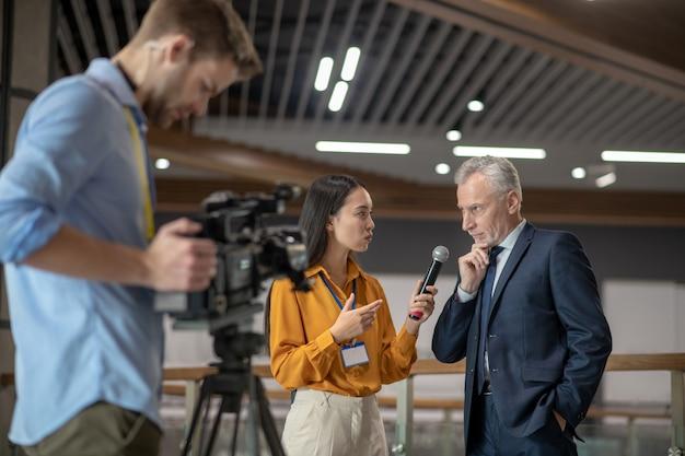 Jonge vrouwelijke verslaggever met interview met beroemde zakenman