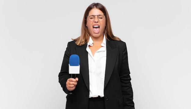 Jonge vrouwelijke verslaggever schreeuwt agressief, kijkt erg boos, gefrustreerd, verontwaardigd of geïrriteerd, schreeuwt nee