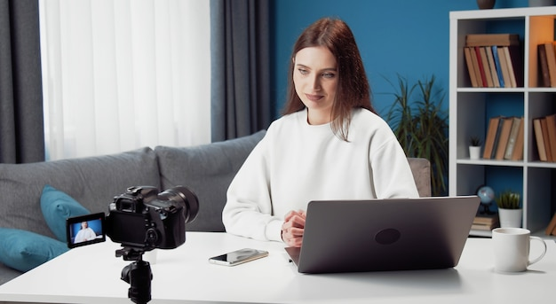 Jonge vrouwelijke vlogger video-opname op camera zit aan bureau voor laptop thuis