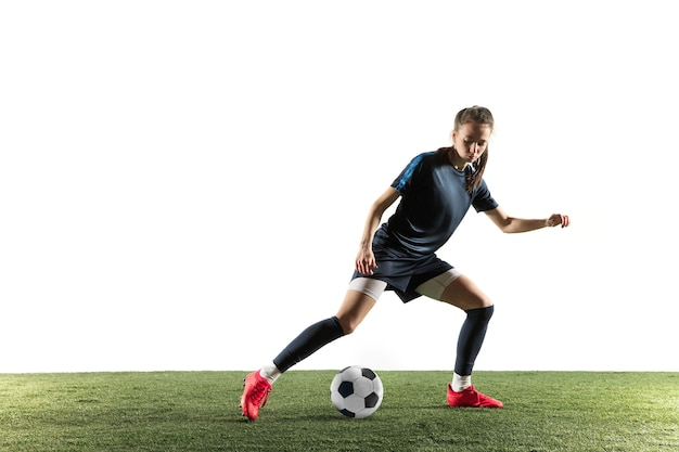 Jonge vrouwelijke voetbal of voetballer met lang haar in sportkleding en laarzen die bal voor het doel in sprong schoppen die op witte achtergrond wordt geïsoleerd. concept van een gezonde levensstijl, professionele sport, hobby.