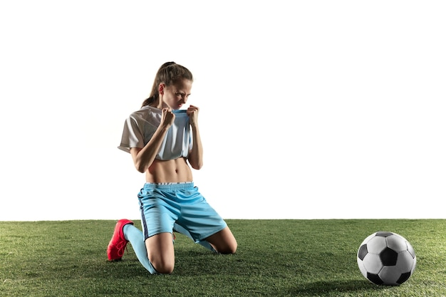 Jonge vrouwelijke voetbal of voetballer met lang haar in sportkleding en laarzen die met de bal zitten die op witte achtergrond wordt geïsoleerd. concept van een gezonde levensstijl, professionele sport, hobby.