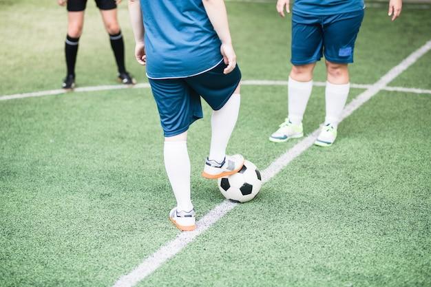 Jonge vrouwelijke voetballer die rechtervoet op voetbal houdt terwijl hij voor een ander meisje op het veld staat