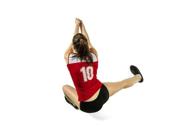 Jonge vrouwelijke volleyballspeler die op witte achtergrond wordt geïsoleerd.