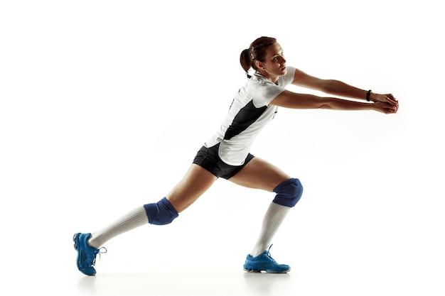 Jonge vrouwelijke volleyballspeler die op witte muur wordt geïsoleerd. vrouw in sportuitrusting en schoenen of sneakers trainen en oefenen. concept van sport, gezonde levensstijl, beweging en beweging.