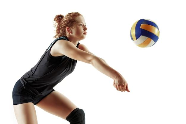 Jonge vrouwelijke volleyballspeler die op witte studioachtergrond wordt geïsoleerd. vrouw in sportuitrusting en schoenen of sneakers trainen en oefenen. concept van sport, gezonde levensstijl, beweging en beweging.