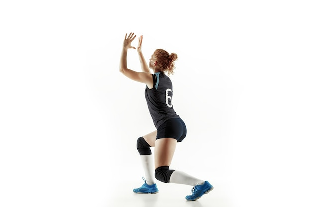 Jonge vrouwelijke volleyballspeler die op witte studioachtergrond wordt geïsoleerd