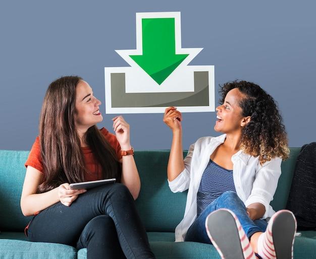 Jonge vrouwelijke vrienden die een downloadpictogram houden