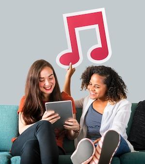Jonge vrouwelijke vrienden die een muzieknootpictogram houden
