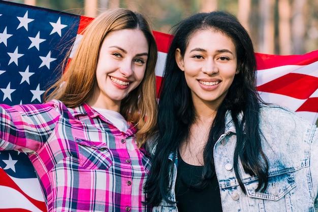Jonge vrouwelijke vrienden die in amerikaanse vlag op onafhankelijkheidsdag golven