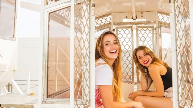 Jonge vrouwelijke vrienden die in de cabine van het ferriswiel genieten van