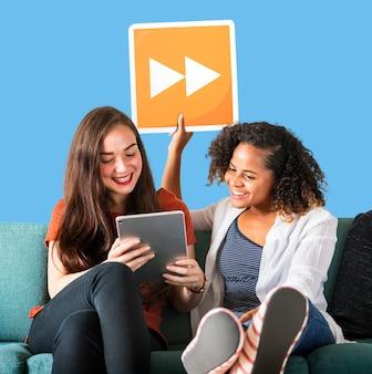 Jonge vrouwelijke vrienden houden een pictogram fast forward
