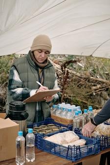 Jonge vrouwelijke vrijwilliger die aantekeningen maakt in document