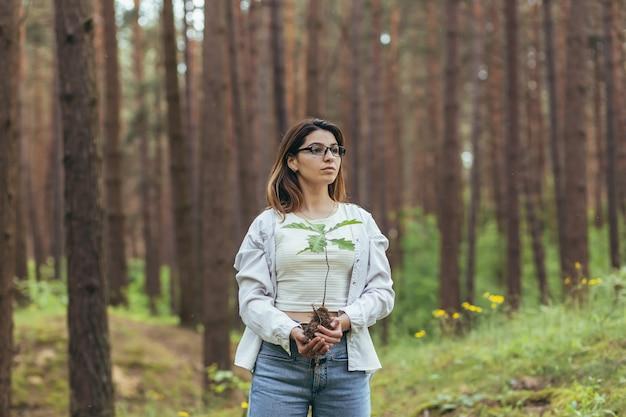 Jonge vrouwelijke vrijwilliger plant een bos en houdt een zaailing van een eikenboom in haar handen