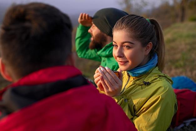 Jonge vrouwelijke wandelaar genieten van warme drank en communiceren met mannen tijdens het rusten tijdens de reis op het platteland