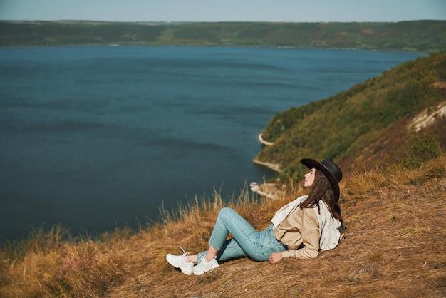 Jonge vrouwelijke wandelaar ontspannen op de bergtop in de buurt van dnjestr
