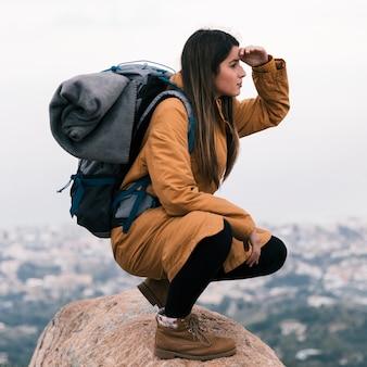 Jonge vrouwelijke wandelaarzitting bovenop rots met haar afscherming van het rugzakoog