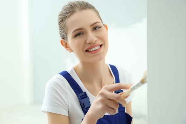 Jonge vrouwelijke werknemer die reparatie in de kamer maakt