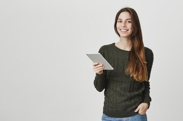 Jonge vrouwelijke werknemer, digitale kunst freelancer met behulp van tablet, glimlachend