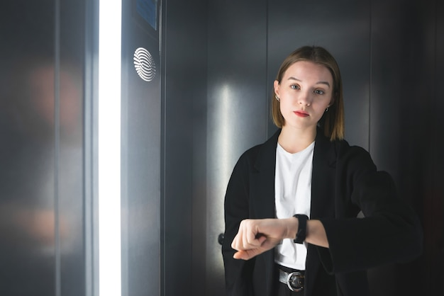 Jonge vrouwelijke werknemer in het pak controleert de tijd in de lift.
