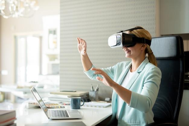Jonge vrouwelijke werknemer in vr-bril aandacht virtuele training zittend door balie in kantoor