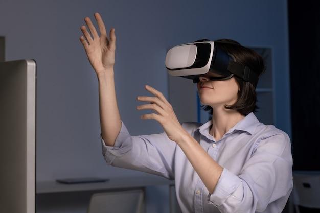 Jonge vrouwelijke werknemer met vr headset zit achter computer in kantoor en virtuele presentatie maken
