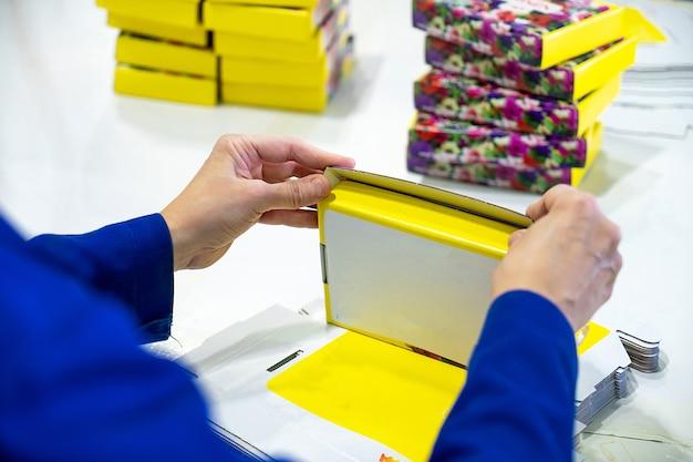 Jonge vrouwelijke werknemer verpakkingsdozen voor verzending in magazijn.