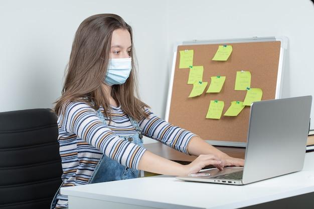 Jonge vrouwelijke werknemer werkzaam in het kantoor in masker en met behulp van preventieve maatregelen