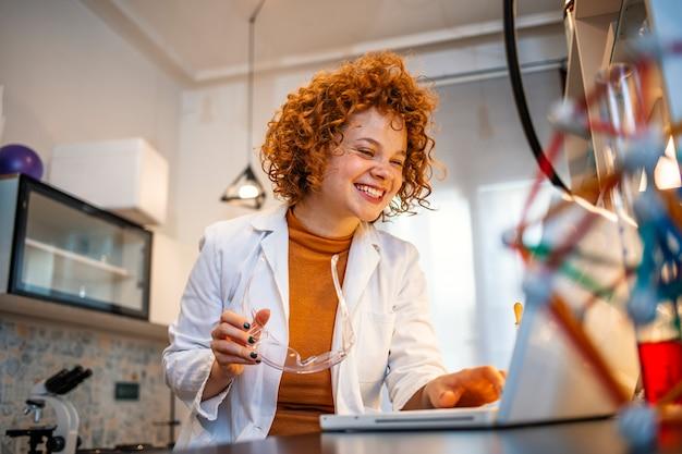 Jonge vrouwelijke wetenschapper die aan de computer in een laboratorium werkt. vrouwelijke onderzoeker die aantekeningen maakt op haar werkplaats.
