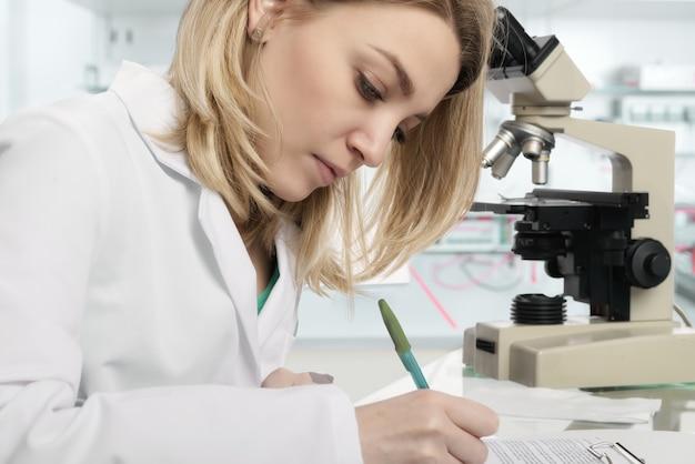 Jonge vrouwelijke wetenschapper die in modern laboratorium schrijft