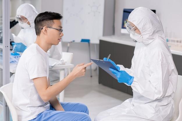 Jonge vrouwelijke wetenschapper in beschermende bril, masker en overall, aantekeningen maken in document tijdens het raadplegen van chinese man in het laboratorium