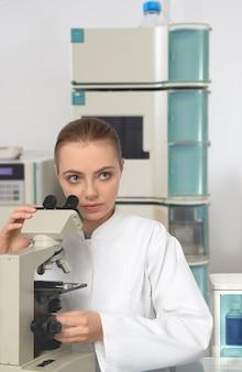 Jonge vrouwelijke wetenschapper in witte laboratoriumlaag die met een microscoop werkt