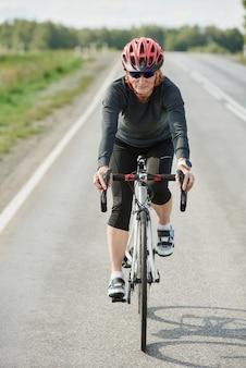 Jonge vrouwelijke wielrenner in sportkleding die buiten op een weg racet