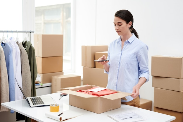 Jonge vrouwelijke winkelbediende fotograferen pakket met gevouwen vrijetijdskleding voordat ze de doos inpakken en naar de klant verzenden