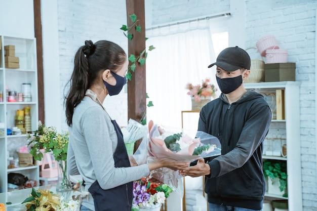 Jonge vrouwelijke winkelier die een gezichtsmasker en een schort draagt. het onderhouden van mannelijke kopers van flanellen bloemen in de bloemenwinkel