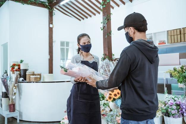 Jonge vrouwelijke winkelier die een gezichtsmasker en een schort draagt. mannelijke flanellen bloemenkopers in de bloemenwinkel bedienen met protocol gezond