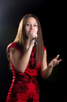 Jonge vrouwelijke zangeres in rode jurk