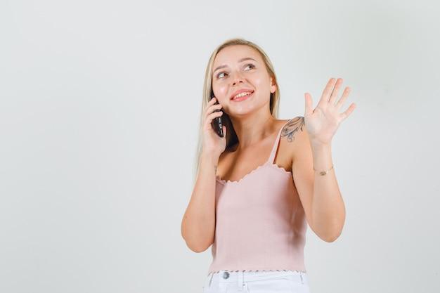 Jonge vrouwelijke zwaaiende hand tijdens het praten over smartphone in singlet