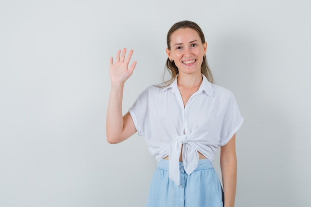 Jonge vrouwelijke zwaaiende hand voor begroeting in blouse en rok en op zoek gemoedelijk