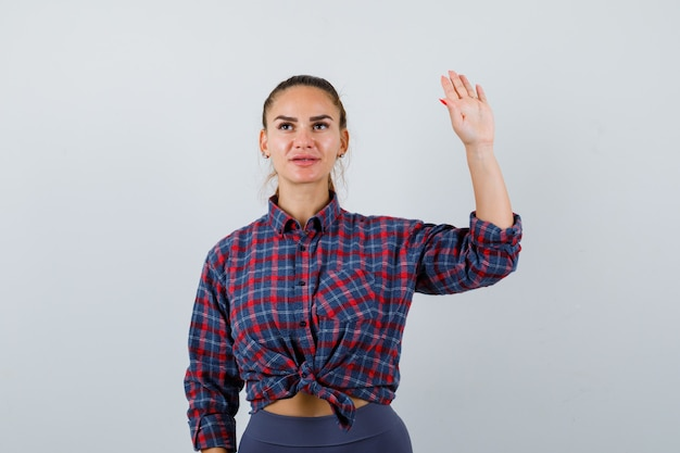 Jonge vrouwelijke zwaaiende hand voor begroeting in geruit hemd, broek en zelfverzekerd, vooraanzicht.