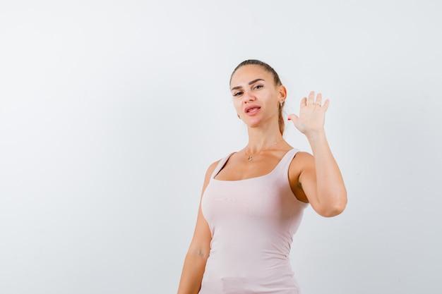 Jonge vrouwelijke zwaaiende hand voor begroeting in wit mouwloos onderhemd en op zoek gelukkig, vooraanzicht.