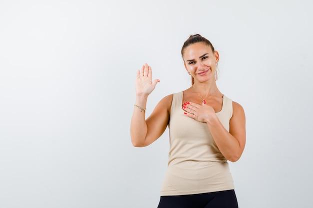 Jonge vrouwelijke zwaaiende hand voor groet in beige mouwloos onderhemd en op zoek gelukkig, vooraanzicht.