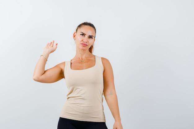 Jonge vrouwelijke zwaaiende hand voor groet in beige mouwloos onderhemd en op zoek zelfverzekerd