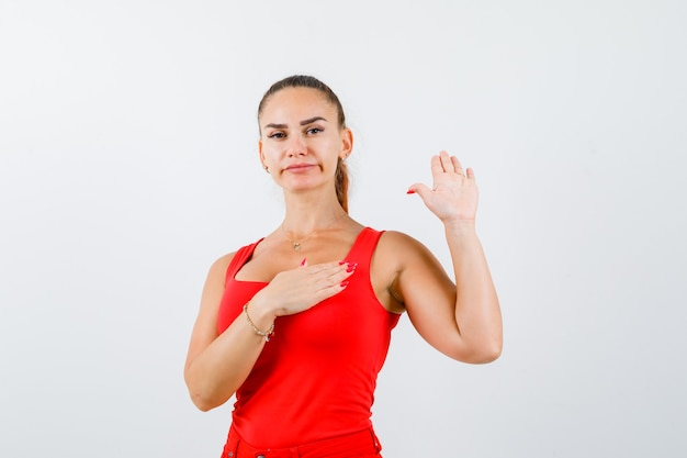 Jonge vrouwelijke zwaaiende hand voor groet in rode tanktop, broek en er zelfverzekerd uitzien. vooraanzicht.