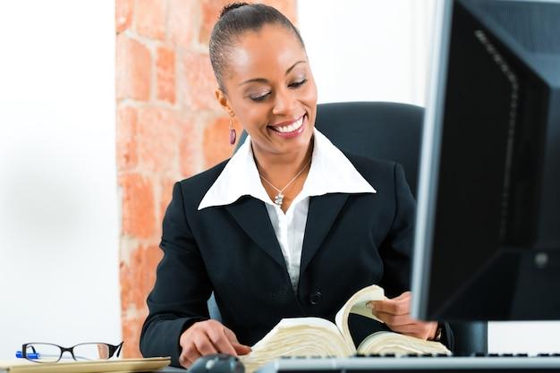 Jonge vrouwelijke zwarte advocaat die in haar bureau werkt en een typisch wetboek achter een computer leest