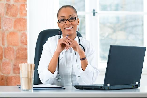 Jonge vrouwelijke zwarte arts zit bij een raam in de kliniek, ze heeft een stethoscoop