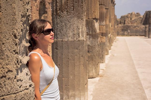 Jonge vrouwen achter de ruïnes van de stad pompeii. italië