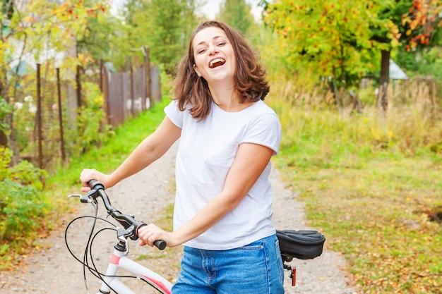 Jonge vrouwen berijdende fiets in het park van de de zomerstad in openlucht. actieve mensen. het hipstermeisje ontspant en ruiterfiets. op de zomerdag naar het werk fietsen. fiets en ecologie levensstijl concept.