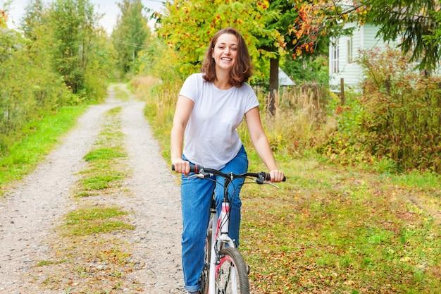 Jonge vrouwen berijdende fiets in het park van de de zomerstad in openlucht